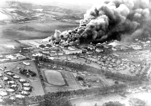 Planes and hangars burning at Wheeler Army Air Field, Oahu, soon after it was attacked in the morning of December 7, 1941. View toward the southwest as seen from a Japanese Navy plane. Naval History and Heritage Command photograph