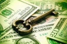 Antique skeleton key on U.S. bills.  Green-toned.