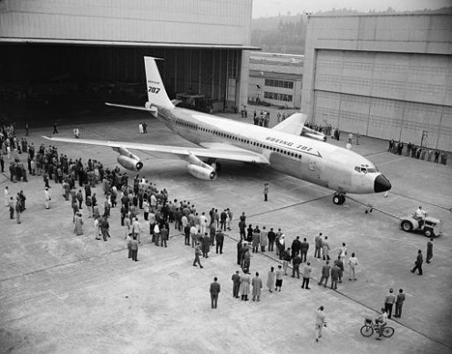 A small crowd of factory workers and officials watches as Boeing Airplane Company rolls America's first jet airliner at Renton, Wash., Monday, Oct 28, 1957. The huge Boeing 707 Jet Stratoliner, capable of carrying 80 to 180 persons 5,000 miles nonstop at speeds of more than 600 miles an hour. The jet will be delivered to Pan American World Airways. (AP Photo)